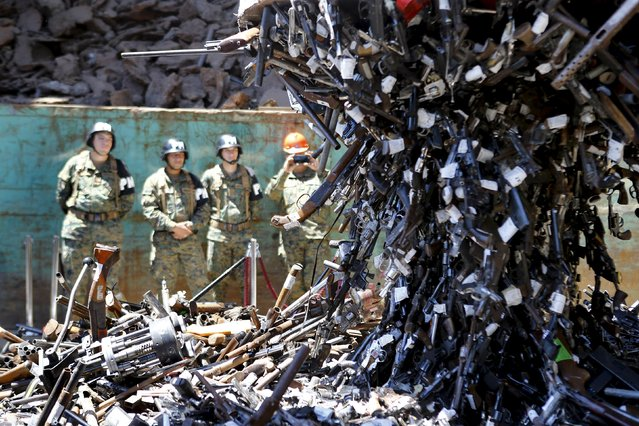 Confiscated weapons hang from a magnet before being destroyed at a foundry in Santiago, Chile, January 18, 2016. (Photo by Ivan Alvarado/Reuters)