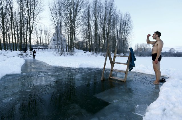 A man crosses himself as he is ready to dip into the icy waters of a lake as part of celebrations for Orthodox Epiphany in Minsk, January 19, 2016. (Photo by Vasily Fedosenko/Reuters)