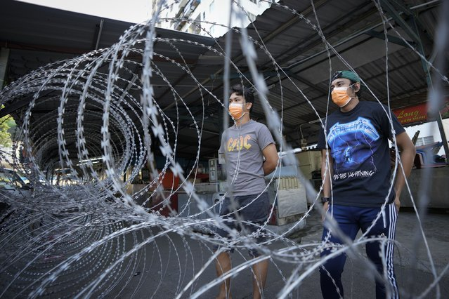 Residents wearing face mask stand behind barbwire outside Pangsapuri Permai, residential area placed under the enhanced movement control order (EMCO) due to drastic increase in the number of COVID-19 cases recorded over the past 10 days in Cheras, outskirt of Kuala Lumpur, Malaysia, Friday, May 28, 2021. Malaysia's latest coronavirus surge has been taking a turn for the worse as surging numbers and deaths have caused alarm among health officials, while cemeteries in the capital are dealing with an increasing number of deaths. (Photo by Vincent Thian/AP Photo)