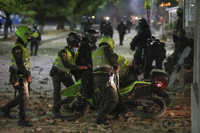 Police aid a fellow officer who slipped on his motorbike during clashes with anti-government demonstrators protesting against the FIFA World Cup Qatar 2022 qualifying soccer match between Argentina and Colombia near the Metropolitano stadium in Barranquilla, Colombia, Tuesday, June 8, 2021. (Photo by Jairo Cassiani/AP Photo)