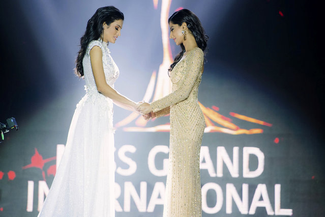 In this October 25, 2018, photo released by Miss Grand International Co., Ltd., finalists, Clara Sosa of Paraguay, left, hold hands with Meenakshi Chaudhary of India before the winner was announced during Miss Grand International 2018 in Yangon, Myanmar. Miss Grand International 2018 Sosa fell while the first runner-up Miss India Chaudhary tried to help. Sosa soon recovered and had a teary smile as she was crowned. (Photo by Miss Grand International Co., Ltd. via AP Photo)