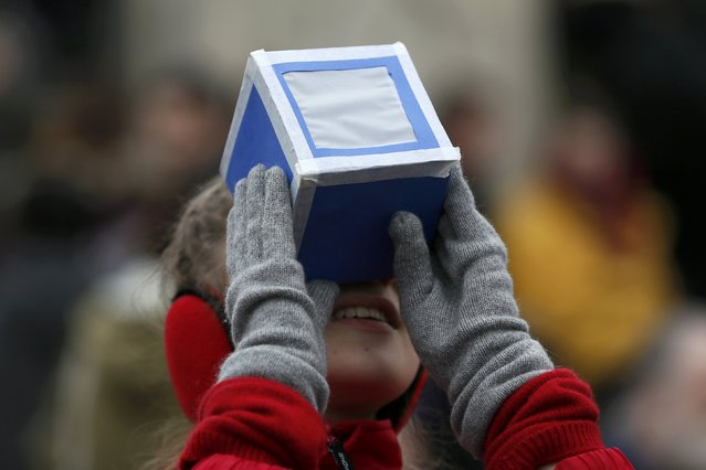 A girl holds a home-made protective viewing box outside The Royal Observatory during a partial solar eclipse in Greenwich, south east London March 20, 2015. (Photo by Stefan Wermuth/Reuters)