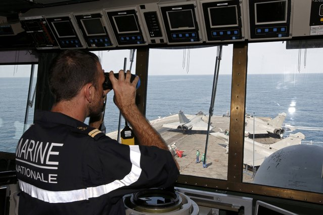 A lieutenant observes Rafale fighter jet movements from the command post aboard France's Charles de Gaulle aircraft carrier in the Gulf, January 27, 2016. (Photo by Philippe Wojazer/Reuters)