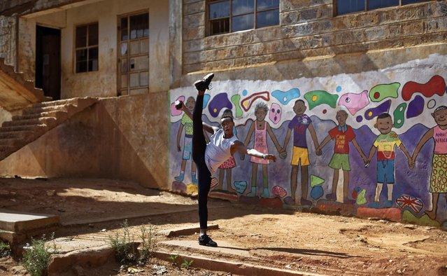 In this photo taken Friday, December 9, 2016, Kenyan ballet dancer Joel Kioko, 16, strikes a pose as a joke as he walks through the courtyard of a school where he was teaching young dancers, in the Kibera slum of Nairobi, Kenya. (Photo by Ben Curtis/AP Photo)