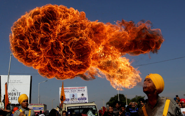 An Indian Sikh devotee spits fire as he performs during religious procession ahead of the birth anniversary of the first Sikh Guru or master, Sri Guru Nanak Dev Ji, the founder of Sikhism, in Jammu, the winter capital of Kashmir, India, 21 November 2018. The birth anniversary of Guru Nanak Dev Ji will be observed on 23 November 2018. (Photo by Jaipal Singh/EPA/EFE)