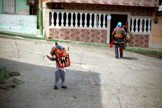 """A boy puts on a mask of the Venezuelan brotherhood """"Dancing Devils"""" during their annual Corpus Christi celebration with a call for the end of the coronavirus disease (COVID-19), in Naiguata, Venezuela on June 3, 2021. (Photo by Leonardo Fernandez Viloria/Reuters)"""