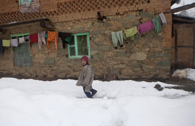 A Kashmiri boy walks in a snow-covered field outside his home in Mahen village, some 41 Kilometer (25 miles) northwest of Srinagar, Indian controlled Kashmir, Tuesday, March 17, 2015. The Jammu-Srinagar highway, connecting the Kashmir valley to the rest of the country, remained closed for the third consecutive day Tuesday following heavy rain and snowfall at some places. (Photo by Dar Yasin/AP Photo)