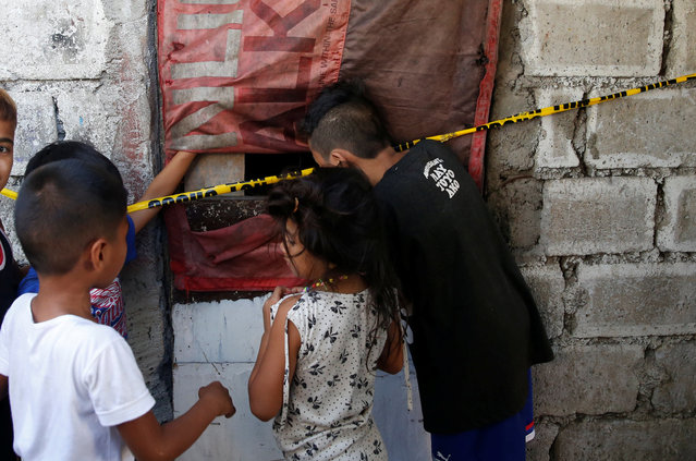 Children look inside a room where 7 people were shot dead by suspected vigilantes at a house storing illegal narcotics, police said on Thursday, in Caloocan city, Metro Manila, in the Philippines December 29, 2016. (Photo by Erik De Castro/Reuters)