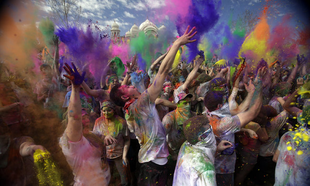 Revelers throw colored corn starch into the air as they celebrate the 2015 Holi (Festival of Colors) at the Krishna Temple in Spanish Fork, Utah on Saturday, March 28, 2015. (Photo by Rick Bowmer/AP Photo)