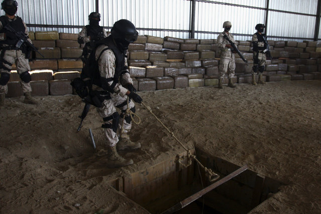 A soldier opens the access to a tunnel as others stand guard near packages containing marijuana during a presentation to the media in Tijuana, November 16, 2011. (Photo by Jorge Duenes/Reuters)