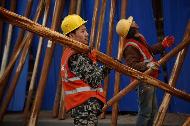 Workers build wooden scaffolding at a construction site in Beijing, China, December 31, 2016. (Photo by Thomas Peter/Reuters)