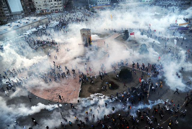 People run away as Turkish riot policemen fire tear gas on Taksim square on June 11, 2013. (Photo by Bulent Kilic/AFP Photo)
