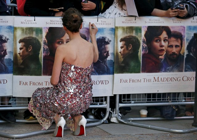 """Actress Carey Mulligan signs a poster at the world premiere of """"Far From the Madding Crowd"""" at the BFI Southbank in London, April 15, 2015. (Photo by Cathal McNaughton/Reuters)"""
