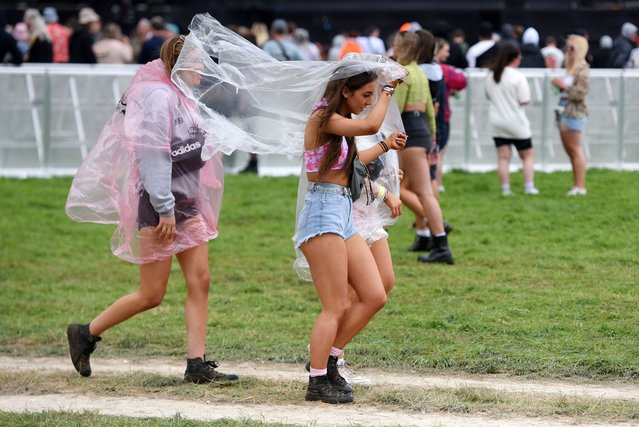 Festival goers put on ponchos as the rain falls on Day 1 of Leeds Festival 2021 at Bramham Park on August 27, 2021 in Leeds, England. (Photo by Matthew Baker/Getty Images)