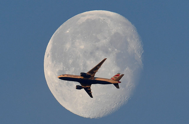 A British Airways passenger plane flies in front of the moon above London, Britain, May 3, 2018. (Photo by Toby Melville/Reuters)