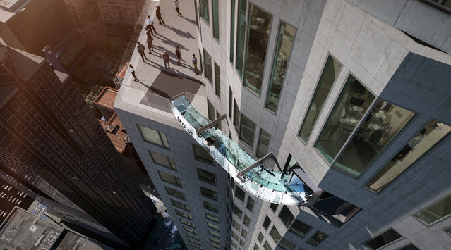 This undated artist's rendering provided by Overseas Union Enterprise Limited shows a glass slide 1,000 feet above the ground off the side of the U.S. Bank Tower in downtown Los Angeles. The 45-foot-long attraction is part of a $50 million renovation that will also put a bar and open-air observation deck on the top floors of the 72-story building. (Photo by Michael Ludvik/OUE Ltd. via AP Photo)