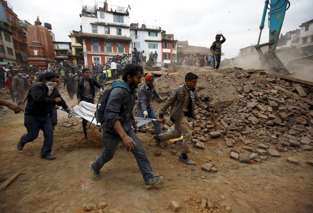People carry the body of a victim on a stretcher, which was trapped in the debris after an earthquake hit, in Kathmandu, Nepal April 25, 2015. (Photo by Navesh Chitrakar/Reuters)