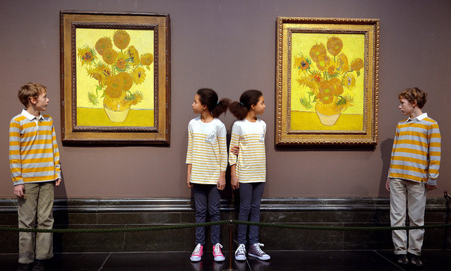 A pair of Vincent Van Gogh's Sunflower paintings hang side-by-side and are studied by twins Edgar and Gabriel, and Eva and Ellie (no surnames supplied), before going on show to the general public on 25th January-27th April 2014, at the National Gallery in Trafalgar Square in central London. (Photo by John Stillwell/PA Wire)