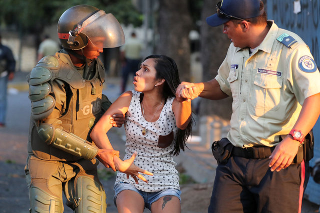 A woman is detained by security forces after looting broke out during an ongoing blackout in Caracas, Venezuela, March 10, 2019. (Photo by Ivan Alvarado/Reuters)