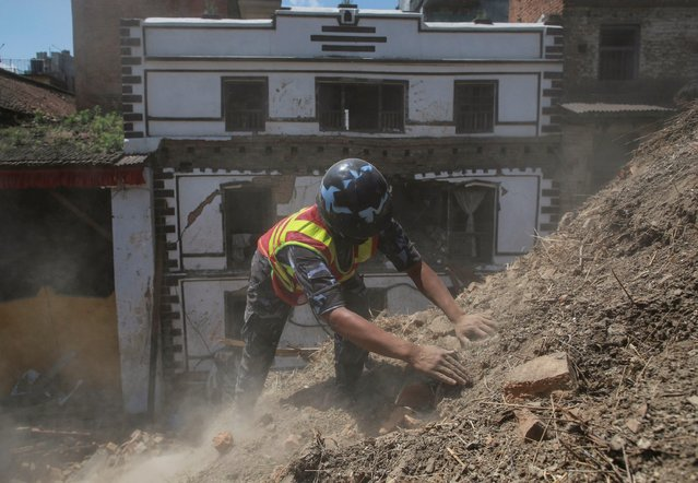 A member of Nepalese police personnel clears rubble with his hands while looking for survivors in the compound of a collapsed temple following Saturday's earthquake in Kathmandu, Nepal, April 27, 2015. (Photo by Danish Siddiqui/Reuters)