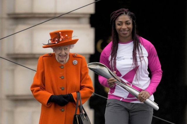 Baton bearer Britain's Kadeena Cox, who won two gold medals at the Rio 2016 Paralympic Games, receives the baton from Britain's Queen Elizabeth II at the Birmingham 2022 Commonwealth Games Queen's Baton Relay event outside Buckingham Palace in London, Thursday, October 7, 2021. The city of Birmingham in England will host the 2022 Commonwealth Games. (Photo by Matt Dunham/AP Photo)