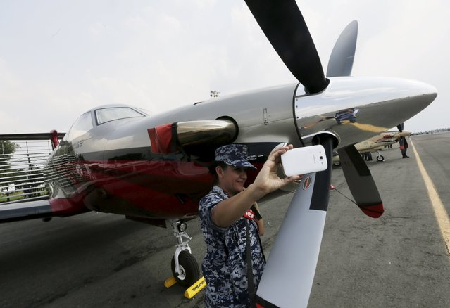 A soldier takes a selfie beside a Pilatus PC-12 after the inauguration of the first Aerospace Fair 2015 at the Santa Lucia military airbase in Tecamac near Mexico City April 22, 2015. (Photo by Henry Romero/Reuters)