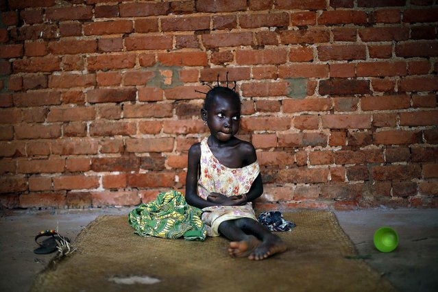 Amandine, 7, who found refuge in the Mbaiki cathedral, in Mbaiki, Central African Republic, lost both parents five years ago, and cannot speak nor walk, on January 26, 2014. She has been in the care of a neighbor since the death of her parents and has been living with dozens of others at the cathedral for the past three weeks, fleeing sectarian violence that has wrecked the country. (Photo by Jerome Delay/Associated Press)