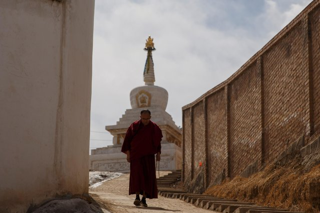 A monk circles the Tibetan Buddhist Kumbum Monastery during a prayer ritual outside Xining, Qinghai province, China on March 10, 2019. (Photo by Thomas Peter/Reuters)