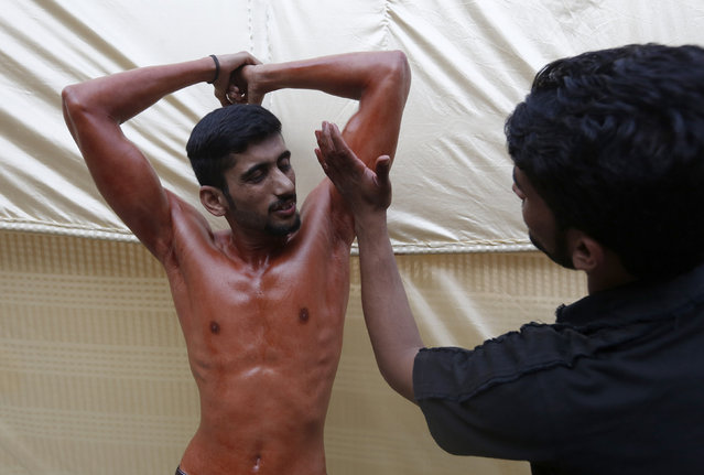 A participant is smeared with oil in preparation for a local bodybuilding and fitness championship in Karachi, Pakistan March 13, 2016. (Photo by Akhtar Soomro/Reuters)