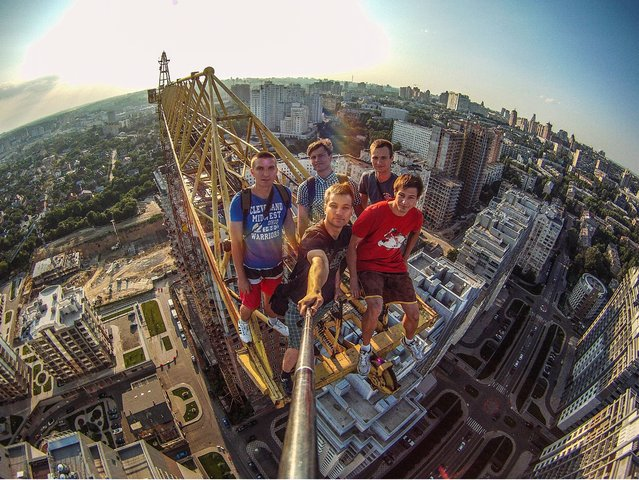 These adrenaline-junkie climbers go to extraordinary lengths, and heights, to take a selfie. Hundreds of metres above the ground, the climbers risk their life and liberty as they scale huge structures and photograph the results. Known as urban exploration, the aim is to find extremely high and almost inaccessible city buildings and reach their dizzying summits.(Photo by Yaroslav Segeda/Solent News)