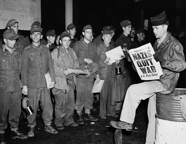 Pfc. Clarence K. Ayers of Evansville, Ind., reads the news of V-E Day as newly arrived German prisoners stand of a New York City pier, May 8, 1945. (Photo by John Rooney/AP Photo)