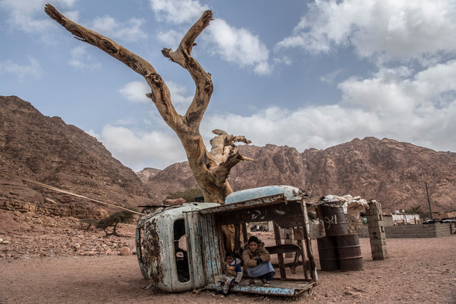 A picture taken on March 30, 2019, shows Egyptian Bedouin children sitting in a rusted shell of a truck in the village of al-Hamada in Wadi el-Sahu in South Sinai governorate. In Wadi Sahu, a village in the southern part of Egypt's eastern Sinai peninsula, made up of humble shacks with corrugated iron and recycled scraps, Bedouins are banking on the return of tourism after the tumultuous years since Egypt's 2011 uprising. (Photo by Khaled Desouki/AFP Photo)