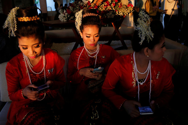 Traditional dancers wait to perform at the Rakhine State Investment Fair at Ngapali beach in Thandwe, Rakhine, Myanmar on February 21, 2019. (Photo by Ann Wang/Reuters)