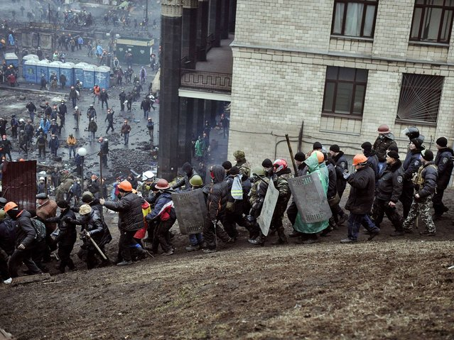 """Protesters escort a """"captured"""" policeman near Independence square in Kiev on February 20, 2014. (Photo by Louisa Gouliamaki/AFP Photo)"""