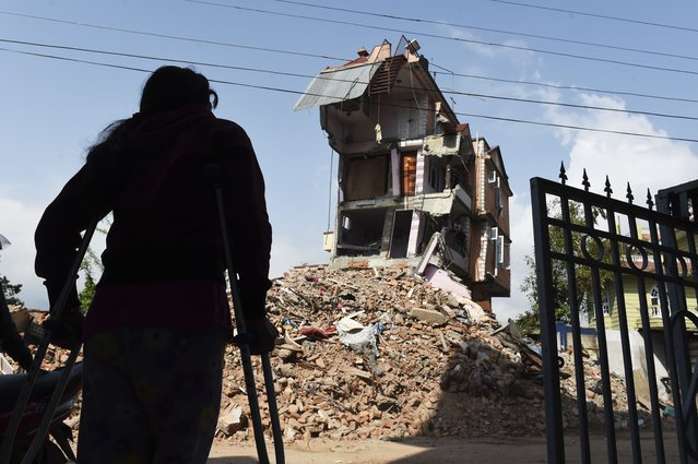 Nepalese resident Nomita Khadka leans on her crutches as she looks at the remains of her home in Kathmandu on May 1, 2015.  Nomita escaped with only a twisted ankle after a devastating earthquake hit the Himalayan nation on May 25.  Desperate survivors living at ground zero of Nepal's earthquake felt abandoned to their fate after losing their loved ones and livelihoods in a disaster that has claimed more than 6,300 lives. (Photo by Roberto Schmidt/AFP Photo)