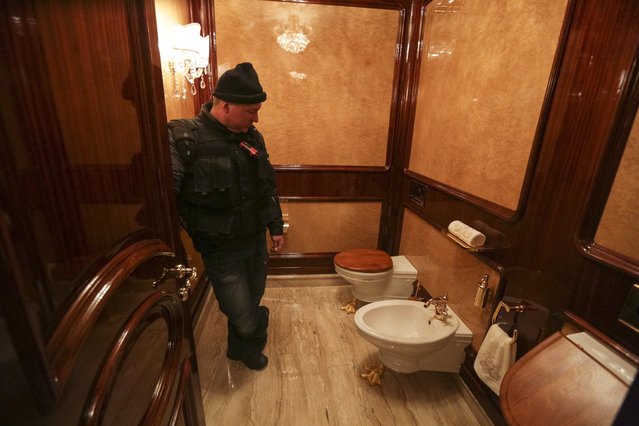 A man stands inside a lavatory as anti-government protesters and journalists walk on the grounds of the Mezhyhirya residence of Ukraine's President Viktor Yanukovich in the village Novi Petrivtsi, outside Kiev February 22, 2014. (Photo by Konstantin Chernichkin/Reuters)