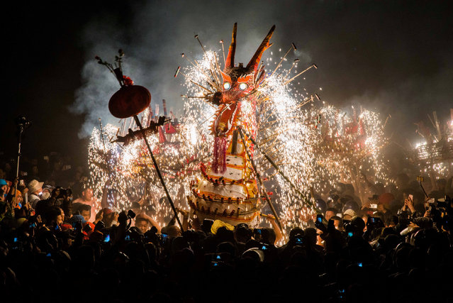 People watch a fire dragon made of lantern, firecrackers and fireworks as people perform a dragon dance to celebrate Lantern Festival in Fengshun county, Guangdong province, China, February 11, 2017. (Photo by Reuters/Stringer)