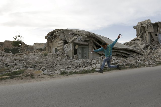 "A boy runs near damaged buildings while competing in ""Freedom Marathon"" marking the fifth anniversary of the Syrian crisis, in the town of Marat Numan in Idlib province, Syria, March 23, 2016. (Photo by Khalil Ashawi/Reuters)"