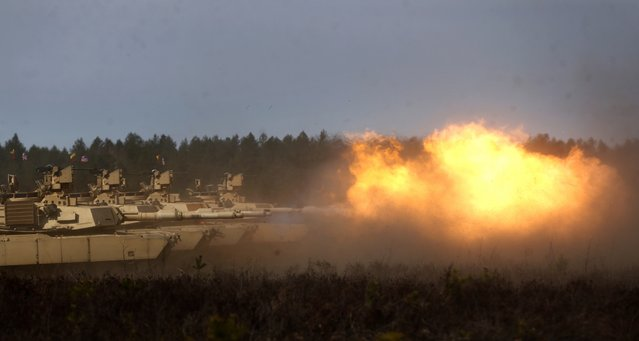 U.S. soldiers from the 2nd Battalion, 1st Brigade Combat Team, 3rd Infantry Division fire their M1A2 Abrams battle tank during a military exercise at the Gaiziunu Training Range in Pabrade some 60km (38 miles) north of the capital Vilnius, Lithuania, Thursday, April 9, 2015. (Photo by Mindaugas Kulbis/AP Photo)
