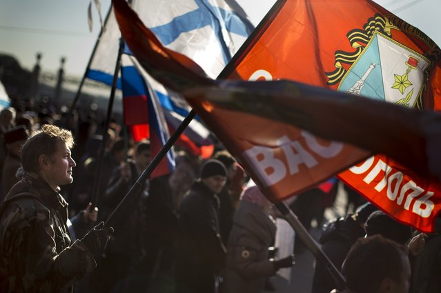 A demonstrator waves a Sevastopol civic  flag during a rally in support of Russian-speaking provinces in eastern and southern Ukraine where many oppose the new authorities in Kiev in Moscow, Russia, Saturday, March 1, 2014. Russian President Vladimir Putin asked parliament Saturday for permission to use the country's military in Ukraine, moving to formalize troop deployments that Ukrainian officials have described as an ongoing invasion of the strategic region of Crimea. (Photo by Alexander Zemlianichenko/AP Photo)