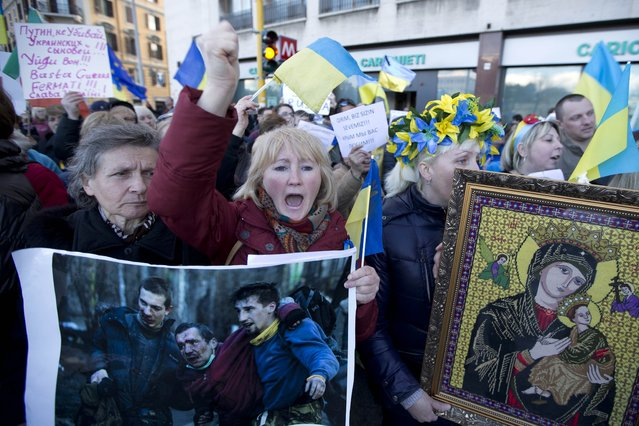 Ukrainians living in Italy shout slogans and hold a photo of what they say are victims of the unrest in Kiev, as they protest outside the Russian embassy, in Rome, Monday, March 3, 2014. Demonstrators condemned Russian military actions in Ukraine. (Photo by Andrew Medichini/AP Photo)