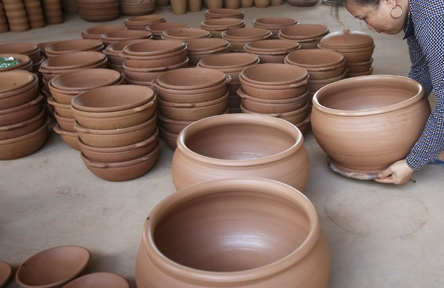A woman puts clay pots and lids to dry at Phu Lang pottery village in Bac Ninh province, Vietnam, May 14, 2015. (Photo by Reuters/Kham)
