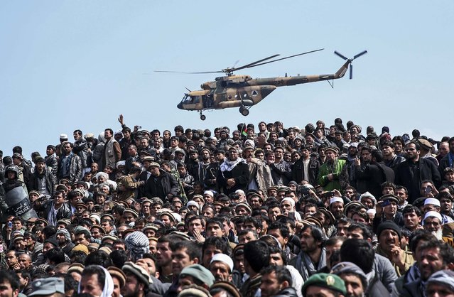 An Afghan National Army helicopter flies over  men attending in the burial of Afghanistan's influential Vice President Mohammad Qasim Fahim during his funeral procession in Kabul, Afghanistan, on March 11, 2014. (Photo by Massoud Hossaini/Associated Press)