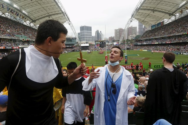 Rugby Union, Hong Kong Sevens, Hong Kong Stadium on April 9, 2016: Fans dressed as a doctor and a priest chat in the stands. (Photo by Bobby Yip/Reuters)