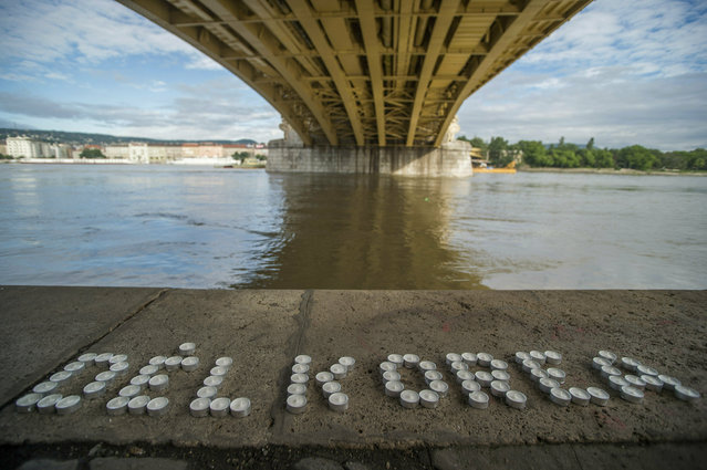 Candles make up the name of South Korea under the Margaret Bridge where a boat carrying South Korean tourists sank in Budapest, Hungary, Friday, May 31, 2019. Late May 29, a hotelship and a smaller cruise ship collided on the River Danube in downtown Budapest, and the latter sank with thirty-three South Korean passengers and two Hungarian staff on board. At least seven people died, seven persons were injured, and twenty-one people went missing. (Photo by Zoltan Balogh/MTI via AP Photo)