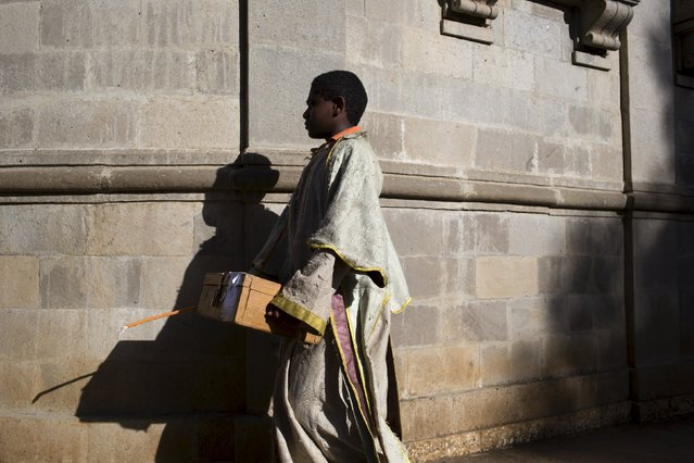 A Christian Orthodox apprentice priest carries a donation box past the walls of a church during Sunday morning mass in the capital Addis Ababa, Ethiopia, May 17, 2015. (Photo by Siegfried Modola/Reuters)