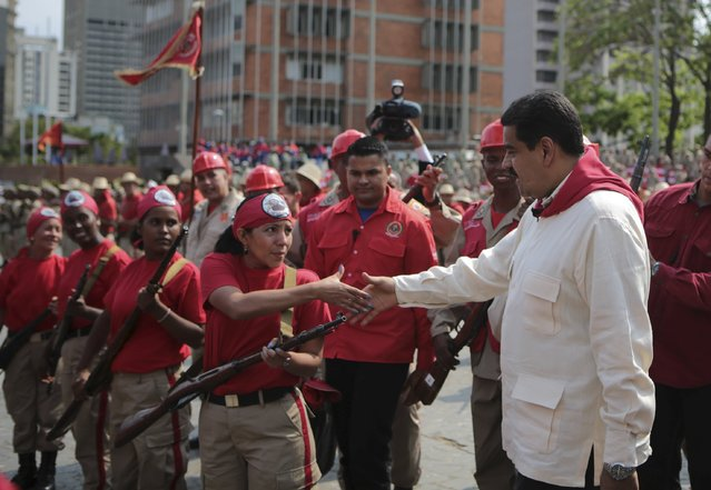 Venezuela's President Nicolas Maduro (R) shakes hands with a militia member during a ceremony in Caracas, in this handout picture provided by Miraflores Palace on April 13, 2016. (Photo by Reuters/Miraflores Palace)