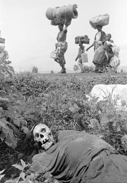 Rwandan refugees pass by the remains of a person who died; 1996. (Photo by Carol Guzy/The Washington Post)