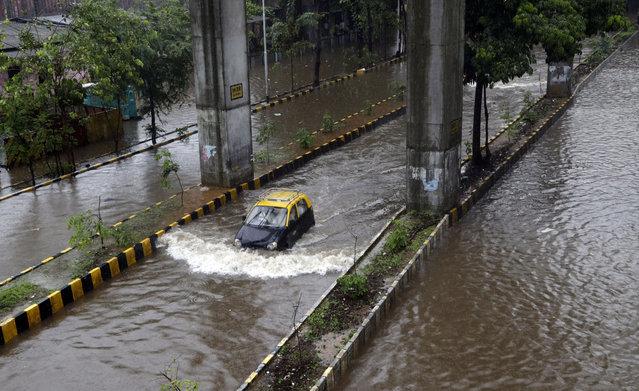 A car moves through a waterlogged street following heavy rains in following heavy rains in Mumbai, India, Tuesday, July 2, 2019. (Photo by Rajanish Kakade/AP Photo)