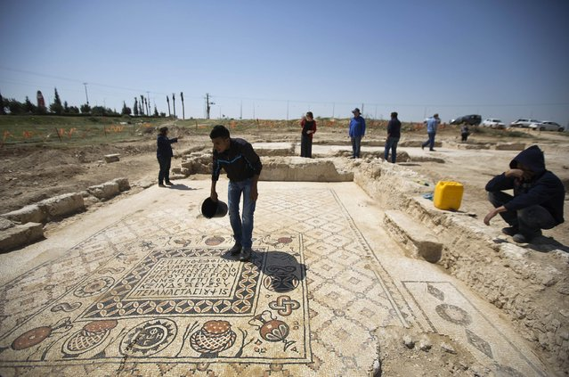 A worker for the Israel Antiquities Authority (IAA) stands on the mosaic floor of a monastery unearthed during excavations in Hura, east of Beersheba April 1, 2014. The IAA said on Tuesday that the Byzantine-era monastery and the mosaic floor were discovered during a salvage dig ahead of construction of an interchange. (Photo by Amir Cohen/Reuters)